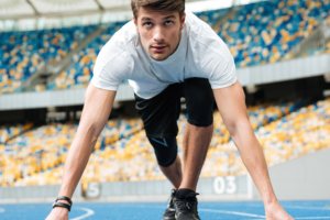 man is in starting position to start running on a track, his eyes look determined
