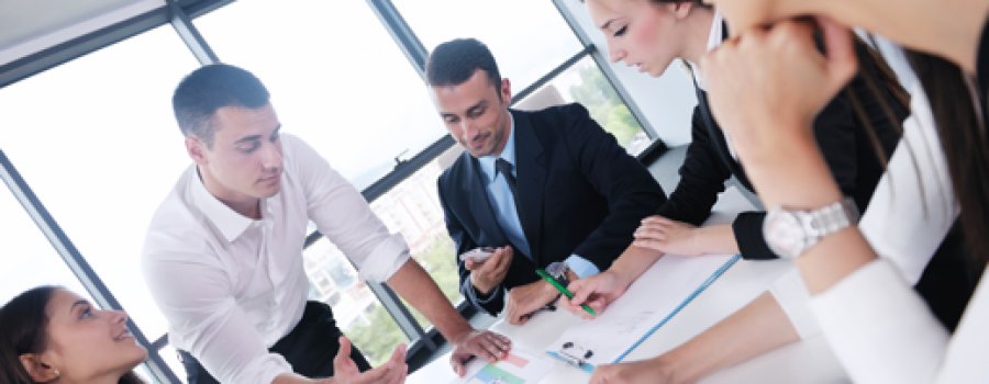 Great Salespeople discuss a during a meeting, 3 women and 2 men point at papers.
