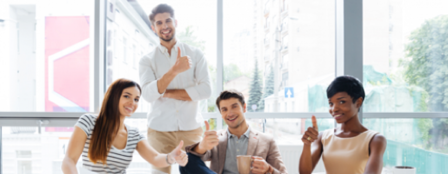 A group of business casual, young professionals giving a thumbs up in a well lit conference room.