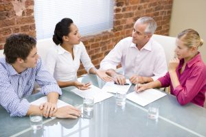 four business people discussing sales and strategy
