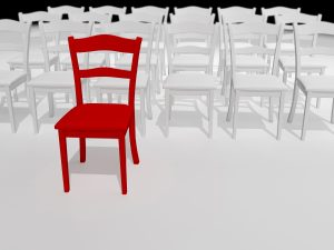 red chair stands out against a bunch of white ones, represents leaders standing out.