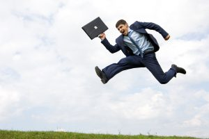 Leaping to conclusions, assuming, jumping to conclusions - Michael Beach Coach blog, Handsome businessman in suit leaping over green grass with cloudy sky at background
