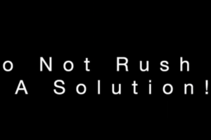 Black screen has white letters that say Do Not Rush A Solution - a video grab from Michael Beach Coaching videos.
