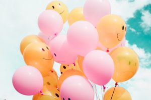 yellow and pink balloons with smiley and sad faces